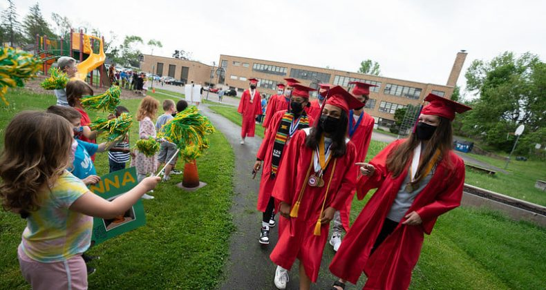 high school graduates walk near young students