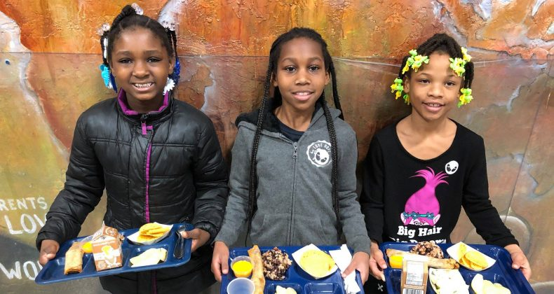 three students holding lunch trays