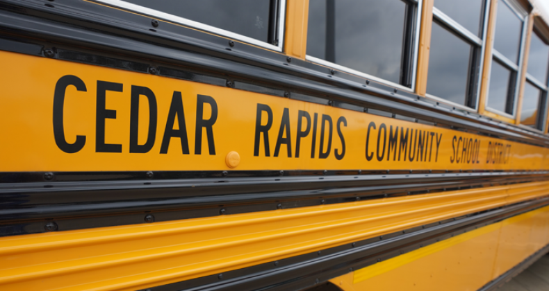 Outside of a school district bus that says, Cedar Rapids