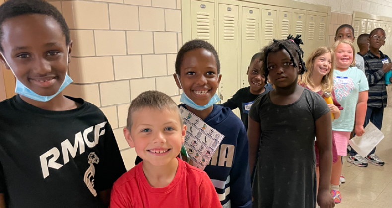 Students smiling in the hallway.