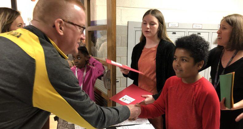 man shaking student's hand