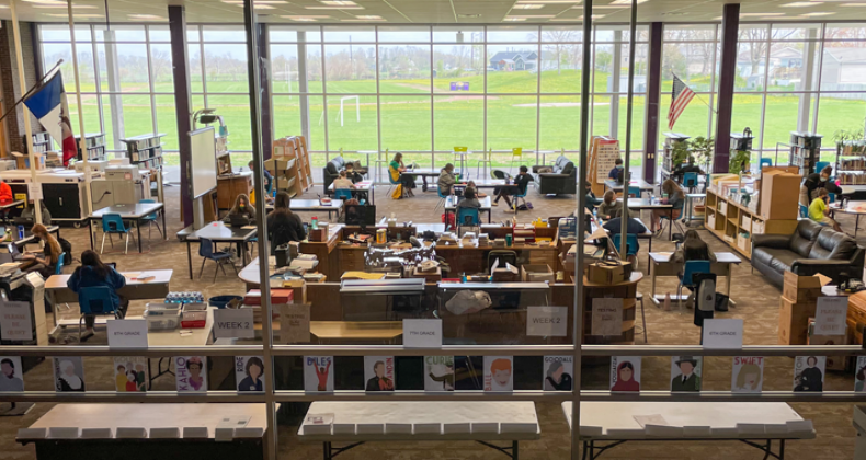 Looking through the windows to a schools IMC where students are working