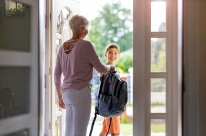 Mother and son with backpack in entrance hall