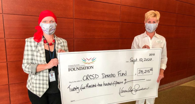 Karen Swanson and Noreen Bush holding a large donation check