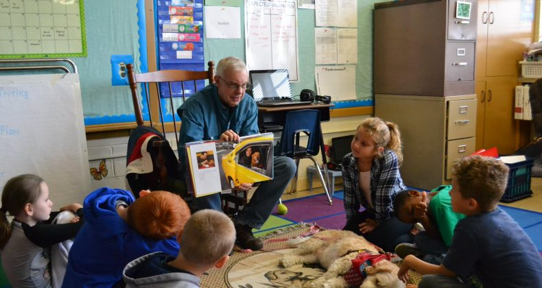 volunteer with dog reading to group of students