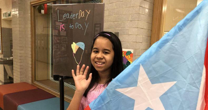 student waving near flag