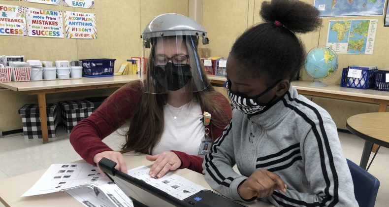 teacher wearing face shield and mask teaching student wearing mask