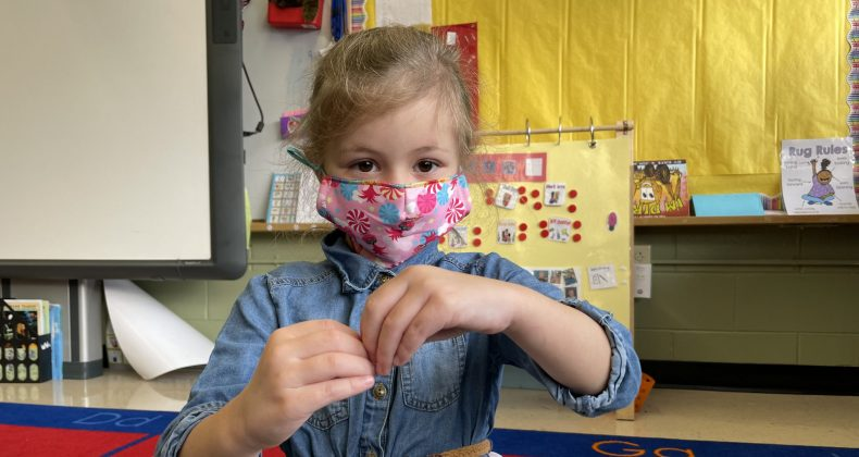 young student with hands together wearing mask