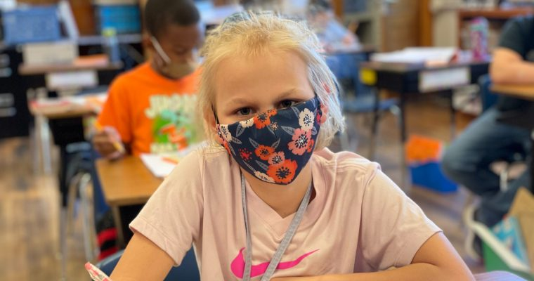 young student wearing mask looking up from desk