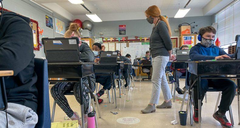 teacher walking around to students sitting at desks in classroom