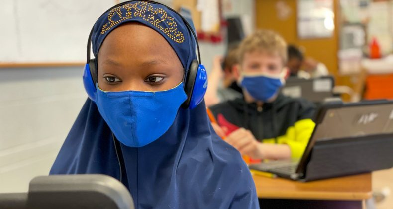 student wearing mask and headphones while looking at laptop