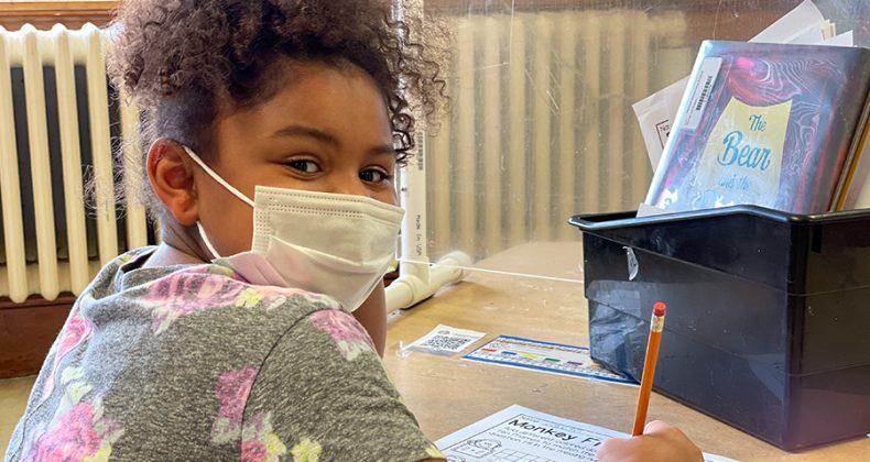 student wearing mask at desk looking over shoulder