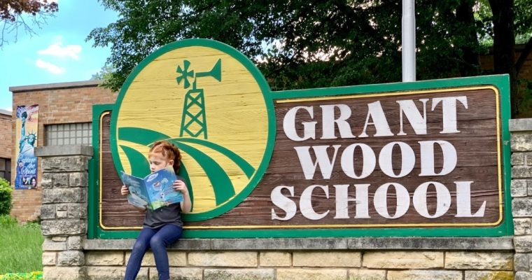student reading book on grant wood elementary school sign