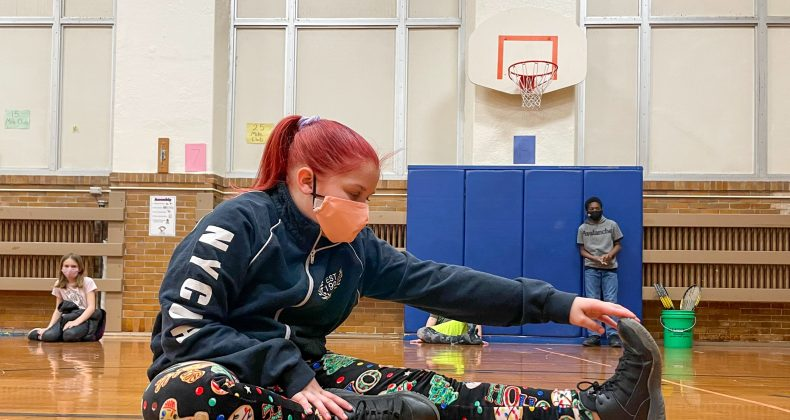 student wearing mask stretching on gym floor