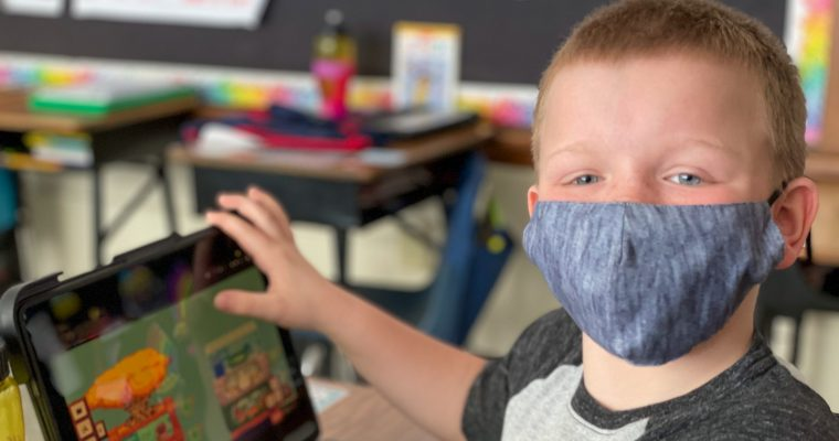 student wearing mask with tablet at desk