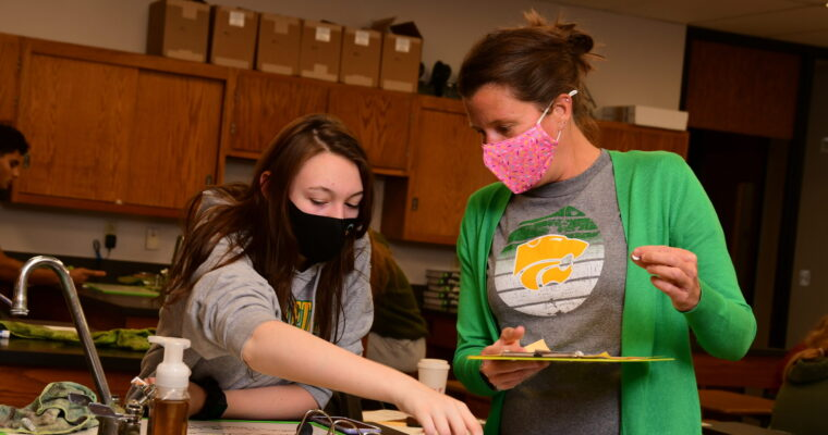 Ms. Stephens works with a student in science class