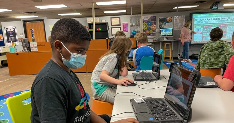 student wearing mask working on laptop at desk in classroom