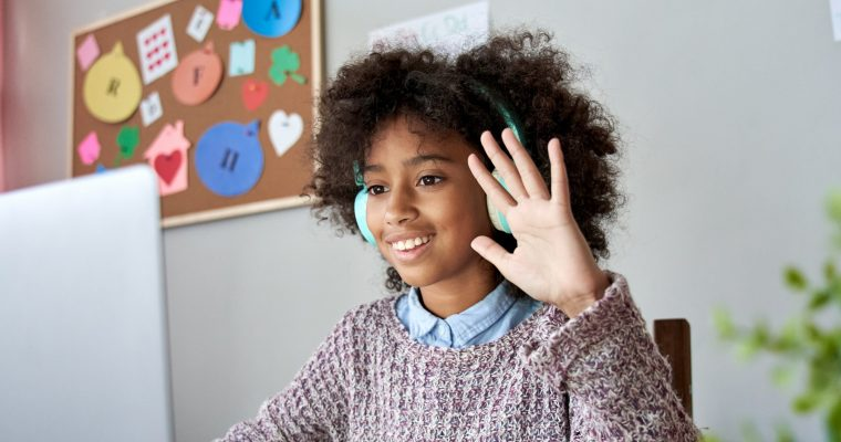 African kid girl waving hand video call remote learning on laptop computer.