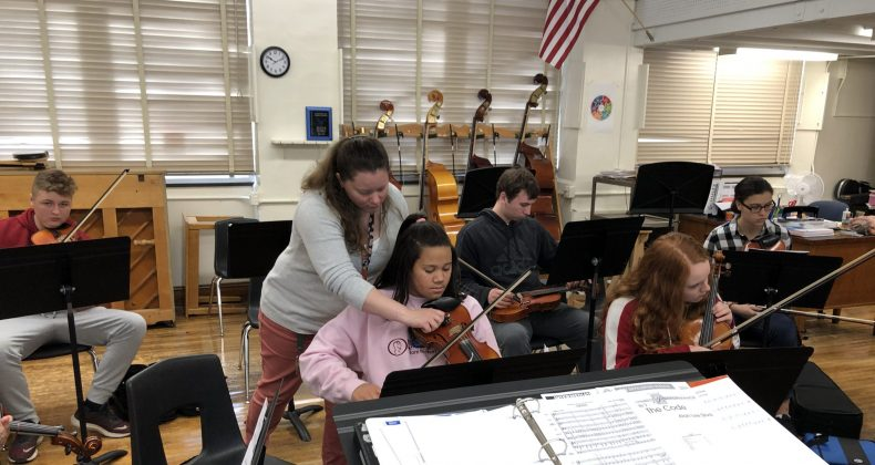 teacher working with student in orchestra