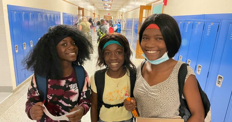 three students smiling together in hallway